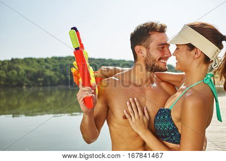 Couple in love hugging at a lake with squirt guns in summer