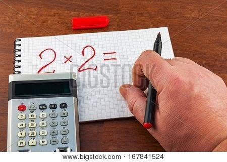 On the notebook sheet in a cage man's hand writes the equation