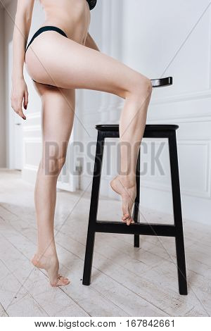 Healthy body. Legs of a girl standing on wooden floor while right arm is in the air, right leg is on the chair