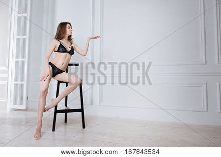 Take a picture. Pretty slim female wearing black lace underwear sitting in semi position while touching her leg