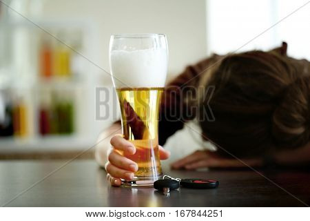 Drunk woman sitting at table with beer and car key, closeup. Don't drink and drive concept