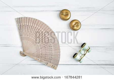 Overhead flat lay shot of feminine objects a woman uses in preparation for a visit at the opera or theater: lorgnette and wooden fan candles. Vintage flat lay top view