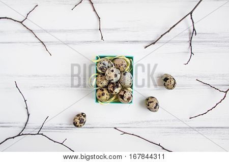 Easter floral background quail eggs in a bright blue box decorated with yellow raffia ribbon and tree branches on vintage wooden table. Flat lay top view view from above
