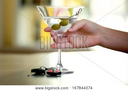 Female hand with glass of alcoholic beverage and car key on table. Don't drink and drive concept