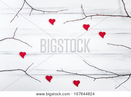 Minimalistic frame with tree branches and woolen hearts on white vintage wooden table. Flat lay top view with a copy space for your text