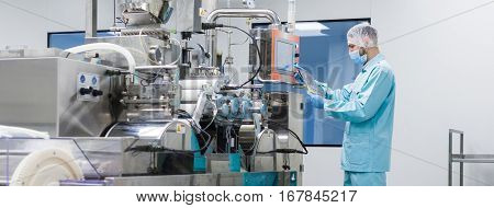 widescreen picture caucasian scientist in blue lab suit trying to fix manufacture machine with shafts in clean factory poster