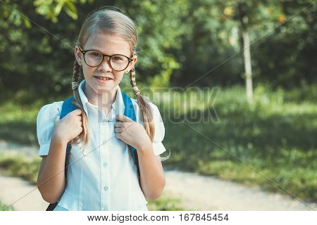 Smiling Young School Child In A School Uniform Standing Against A Tree