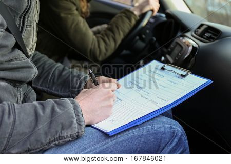 Instructor of driving school giving exam while sitting in car, closeup