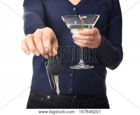 Woman with car key and glass of alcoholic beverage on white background, closeup. Don't drink and drive concept