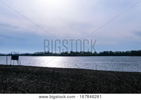 Evening landscape. View of the winter river. Deserted beach with an observation unit.