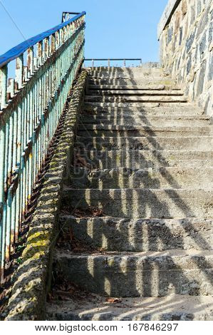 Abandoned staircase with concrete stepping stones and metal handrails illuminated by the sun. View from the bottom up. Sunny day.