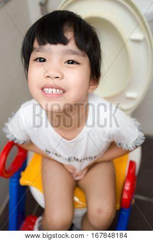 children Asian girl sitting on toilet . .