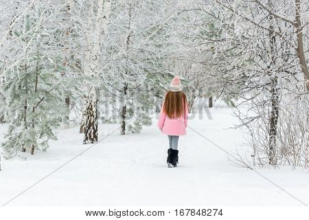 Small girl in a pink jacket walking alone in the snow-covered woods in winter, backview