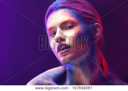 Portrait of young woman with bright body-art in smoke, closeup
