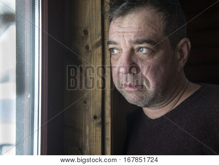 Portrait of pensive sad middle-aged men. He looks out the window.