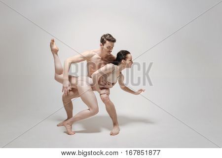Mysterious imagination of the dancers. Delighted pleasant skilled dance couple performing and expressing themselves while demonstrating their skills and flexibility against white background