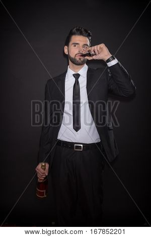 Young Man Drinking Glass Bottle Alcohol Suit Pants Jacket Tie