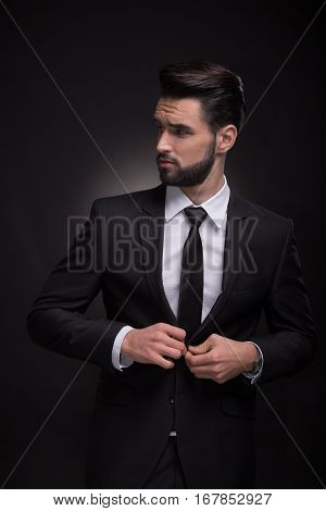 Young Man Elegant Suit Buttoning, Looking Sideways