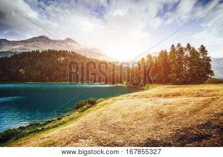 Great view of the azure pond Champfer in alpine valley. Picturesque and gorgeous scene. Location Swiss alps, Silvaplana village. Europe. Retro and vintage style. Instagram toning effect. Beauty world.
