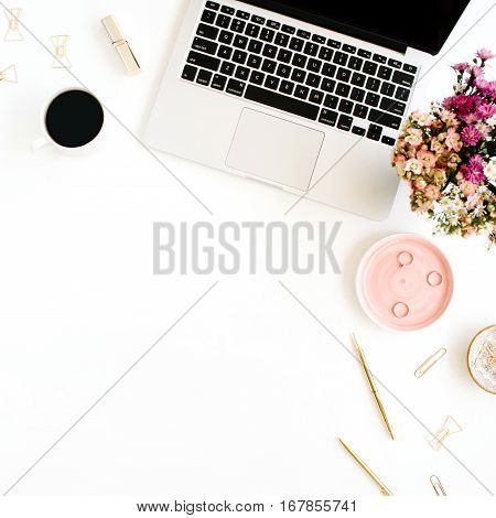 Top view home office desk. Workspace with laptop wildflowers bouquet coffee cup golden pen clips and accessories. Flat lay