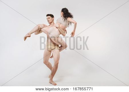 Full of confidence. Calm flexible involved dancers performing isolated in white background and expressing grace and elegance while dancing