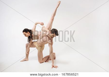 Grace in every movement . Flexile athletic powerful ballet dancers dancing in the white colored studio and showing their flexibility while demonstrating their abilities
