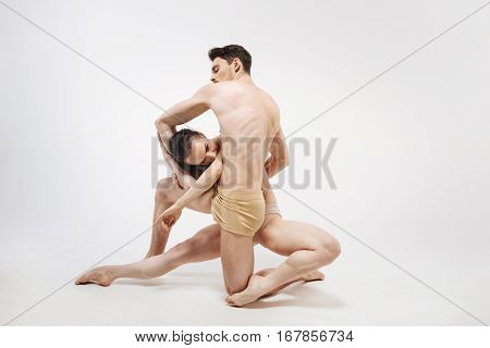 Full of flexibility. Flexile athletic concentrated ballet dancers performing in the white colored studio and showing their flexibility while posing