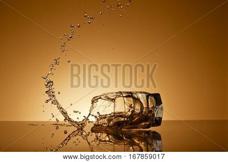 Falling glass of alcoholic drink  on a gold background