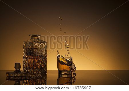 Decanter, glass and flying droplets on a gold background