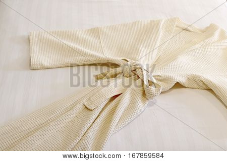 photo of white bathrobe on the bed poster
