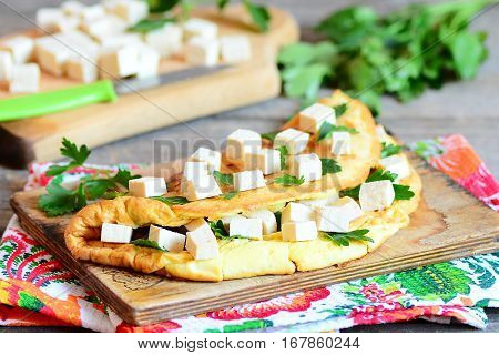 Fried omelet with tofu and parsley on a wooden board. Diced tofu on a cutting board, knife, fresh parsley sprigs, napkin on vintage wooden table. Healthy vegetarian tofu omelet recipe. Closeup