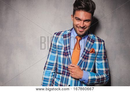 laughing young man in checkered suit and orange tie holding his hand on chest and looks at the camera