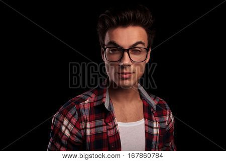 closeup of a young man in checkered shirt and glasses smiling at the camera on black background
