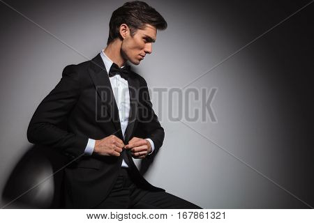 side view of a seated young man in tuxedo buttoning his coat and looks away from the camera in studio against grey background with copyspace