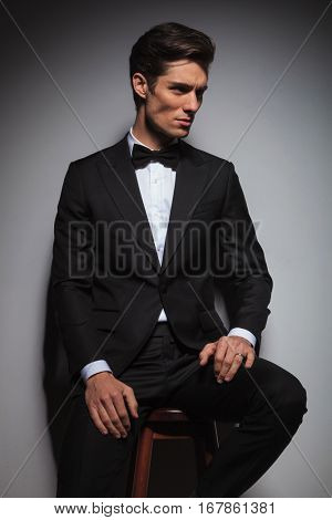 side view of an elegant young business man sitting on a stool wearing a tuxedo and looking away from tehe camera