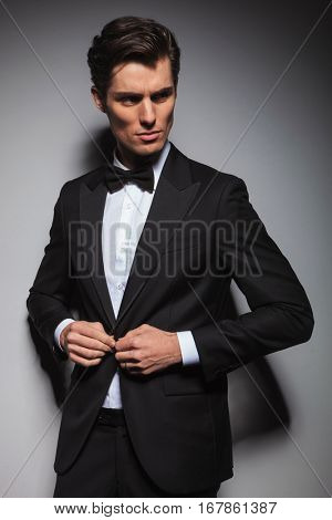 portrait of a young man buttoning his coat and looks back to side , studio portrait on grey background