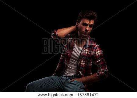 side view of a sexy young casual man sitting and holding hand behind his neck, looks away from the camera on black studio backround
