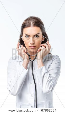 Concentrated female doctor practitioner holding stethoscope and looking at camera