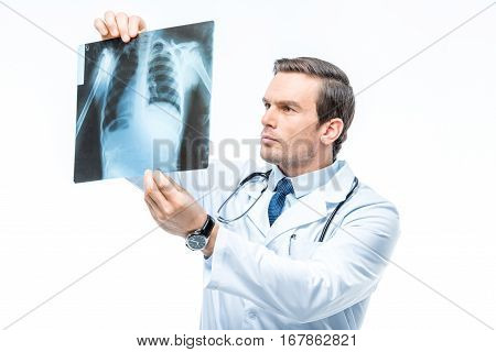 Attentive male doctor practitioner with stethoscope looking at x-ray image on white