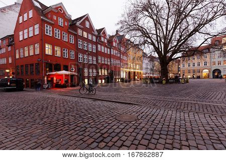 COPENHAGEN, DENMARK - DECEMBER 29, 2016: People on the Grabrodretorv square in winter evening. Dominated by a large plane tree, the square is lined by a number of restaurants with out-door service