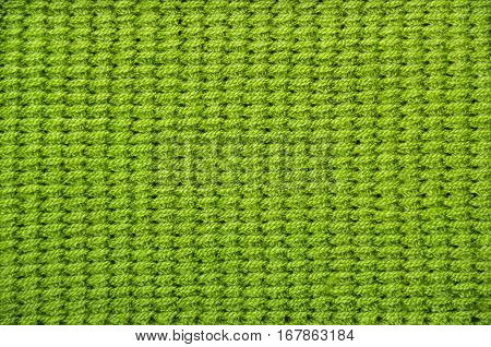 Knitted green background. Green knitted wool texture. Tunisian crochet. Tunisian pattern. Seamless background. Hand-knitted
