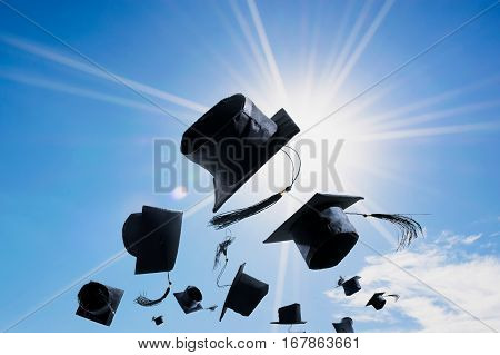 Graduation Ceremony Graduation Caps hat Thrown in the Air with blue sky abstract background.
