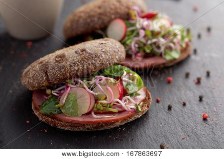 Sandwiches with boar ham, radish, sprouts, and rye bread