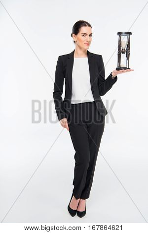 Smiling businesswoman holding hourglass and looking at camera