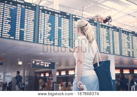 Young blonde woman with shoulder bag, phone and tickets in her hands checking flight timetable in international airport - travel concept