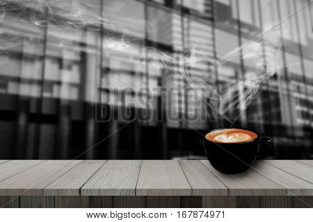 Redolent cappuccino coffee with smoke heart shape on wooden table with blurred modern building.