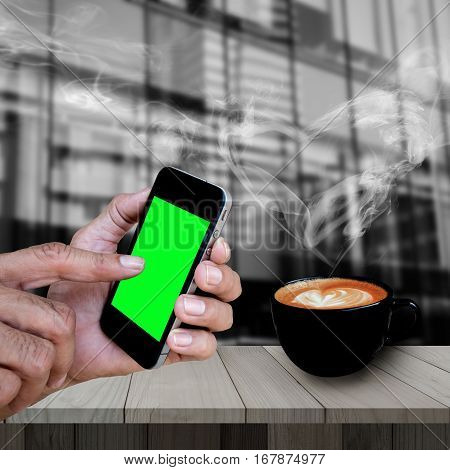 Man hand holding and using smart phone with isolated screen and redolent cappuccino coffee with smoke heart shape on wooden table with blurred modern building.
