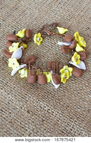 Original bracelet with polymer clay coffee beans and plastic flowers and leaves on burlap