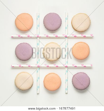 Creative concept photo of macaroons and straws as noughts and crosses game.
