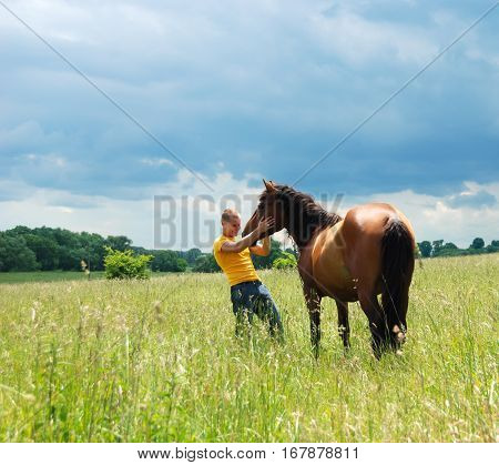 young man and his stallion in a field